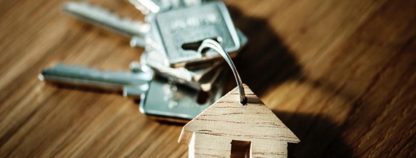 A ring of keys with a wooden house keychain.